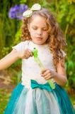 Den lyckliga lilla lockiga flickan som spelar med såpbubblor på en sommarnatur som bär en blått, gå i ax tigertillbehör över henn Royaltyfri Bild