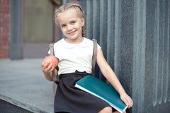 Den lyckliga lilla skolflickan med blont hår i skolalikformig med lunch, bok sitter nära skola arkivbilder