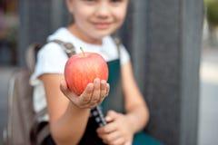 Den lyckliga lilla skolflickan med blont h?r i skolalikformig med lunch, bok sitter n?ra skola arkivbilder