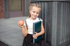 Den lyckliga lilla skolflickan med blont h?r i skolalikformig med lunch, bok sitter n?ra skola fotografering för bildbyråer