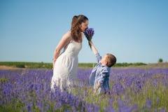 Den lyckliga lilla sonen ger modern för att lukta anstrykningen av en bukett av blommor Arkivbild