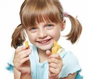 Den lyckliga liten flicka som äter en fransman, steker fotografering för bildbyråer