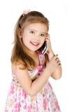 Den lyckliga liten flicka som talar vid cellen, ringer arkivfoto