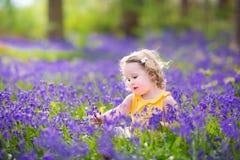 Den lyckliga litet barnflickan i blåklocka blommar i vårskog Royaltyfria Bilder