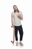 Den lyckliga longboarden och visningen för ung man hållande vaggar tecknet Royaltyfri Fotografi