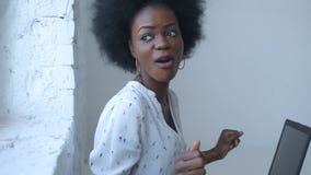 Den lyckliga lyckade afrikanska affärskvinnan dansar på arbetsplatsen, medan sitta på soffan med bärbara datorn
