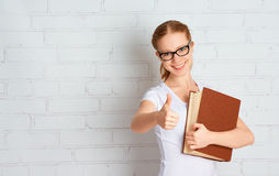 Den lyckliga lyckade studentflickan med bokvisning tummar upp arkivfoton