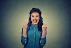 Den lyckliga lyckliga unga kvinnan triumferar pumpa extatiska nävar firar framgång Arkivbilder