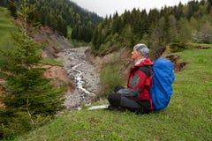 Den lyckliga lycksökaren med ryggsäcken sitter i en bergklyfta fotografering för bildbyråer