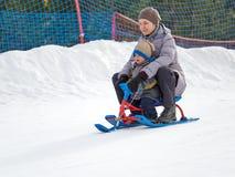 Den lyckliga mamman med sonen rider en släde från berget arkivbild