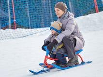 Den lyckliga mamman med sonen rider en släde från berget arkivbilder