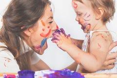 Den lyckliga mamman och behandla som ett barn att spela med den målade framsidan vid målarfärg Royaltyfria Foton