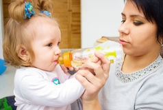Den lyckliga mamman och behandla som ett barn flickan som dricker från flaskan Begreppet av barndom och familjen Den härliga mode Arkivfoto