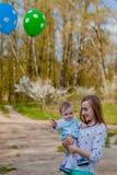 Den lyckliga mamman och behandla som ett barn hållen ballongerna, mamma, och barn har upp gyckel i sommarnaturen, händer, frihets royaltyfria foton