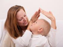 Den lyckliga mamman och behandla som ett barn pojken Arkivbild