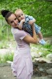 Den lyckliga mamman och behandla som ett barn pojken som kramar och skrattar. Härlig moder och hennes barn utomhus Arkivbilder