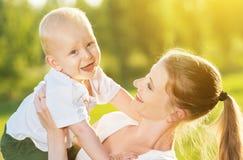 Den lyckliga mamman och behandla som ett barn sonen i sommarnatur arkivbilder