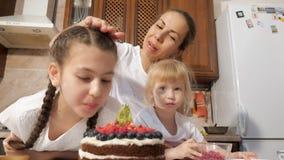 Den lyckliga mamman och döttrar sniffar den lagade mat chokladkakan med bär arkivfilmer