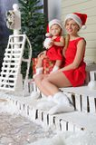 Den lyckliga mamman och dottern i dräkter för jultomten` s sitter under snö Arkivbilder