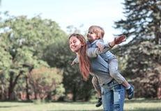 Den lyckliga mamman och hennes son på går i sommaren parkerar royaltyfria bilder