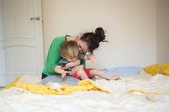 Den lyckliga mamman som spelar med hennes son bäddar ned in, en avkopplad morgon Arkivbild