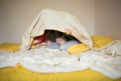 Den lyckliga mamman som spelar med hennes son bäddar ned in, en avkopplad morgon Royaltyfri Bild