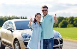 Den lyckliga man- och kvinnavisningen tummar upp på bilen Arkivbild