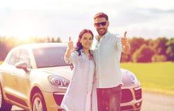 Den lyckliga man- och kvinnavisningen tummar upp på bilen Royaltyfri Fotografi