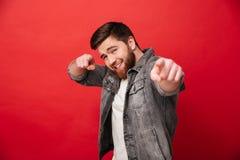 Den lyckliga man30-tal i jeans klår upp med den flirty blicken som poserar på kamera Arkivfoto