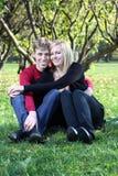 Den lyckliga manen och kvinnan omfamnar och sitter på grönt gräs Fotografering för Bildbyråer
