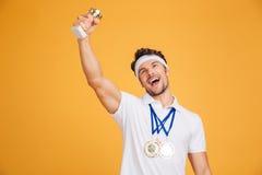 Den lyckliga manidrottsman nen med medaljer och trofén kuper att fira seger Arkivbild
