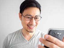 Den lyckliga mannen anv?nder smartphonen Begrepp av att anv?nda p? socialt massmedia royaltyfri fotografi