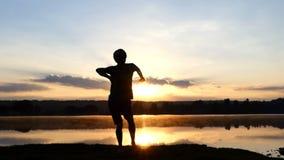 Den lyckliga mannen dansar fri stil på en sjöbank på solnedgången i slo-mo arkivfilmer