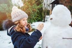 den lyckliga mannen för snö för ungeflickadanande på jul semestrar på trädgård Royaltyfri Bild