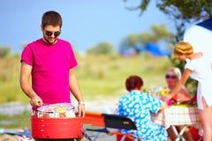 Den lyckliga mannen förbereder mat på gallret, familjpicknick Arkivbilder