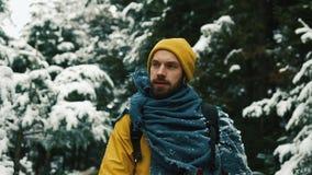 Den lyckliga mannen går över den kalla vinterskogen som täckas med snö stock video