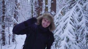 Den lyckliga mannen går i den kalla vinterskogen som vinkar hans hand på kameran räknad snow lager videofilmer