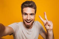 Den lyckliga mannen gör en selfie vid kameran med fred att göra en gest arkivfoto