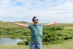 Den lyckliga mannen i solglasögon står i vinden som ser in i himlen Armar är fördelade ut Frihet royaltyfri foto