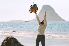 Den lyckliga mannen kastar upp ryggsäcken på havsstranden fotografering för bildbyråer