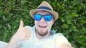 Den lyckliga mannen ligger på ett gräs i en parkera som tar selfie lager videofilmer