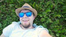 Den lyckliga mannen ligger på ett gräs i en parkera som tar selfie arkivfilmer