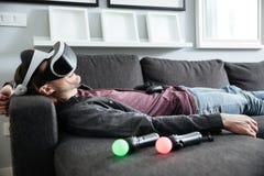 Den lyckliga mannen ligger på hemmastadda bärande exponeringsglas 3d för soffan Arkivfoto