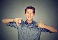 Den lyckliga mannen med tummar tummar ner upp gest Royaltyfri Fotografi
