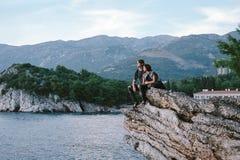 Den lyckliga mannen och kvinnor sitter ner på ett vaggaberg i Montenegro, f royaltyfria foton