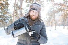Den lyckliga mannen som dricker varmt te från termoset i vinter, parkerar Royaltyfri Fotografi