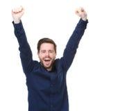 Den lyckliga mannen som ler med armar, lyftte på isolerad vit bakgrund Royaltyfri Foto