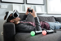 Den lyckliga mannen som sitter hemmastadd lek, spelar med exponeringsglas 3d Royaltyfri Fotografi