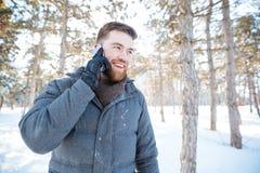 Den lyckliga mannen som talar på telefonen i vinter, parkerar Royaltyfri Fotografi