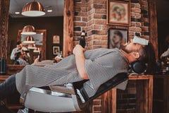 Den lyckliga mannen tycker om hans drink, medan v?nta p? hans barberare p? den moderna frisersalongen royaltyfri fotografi